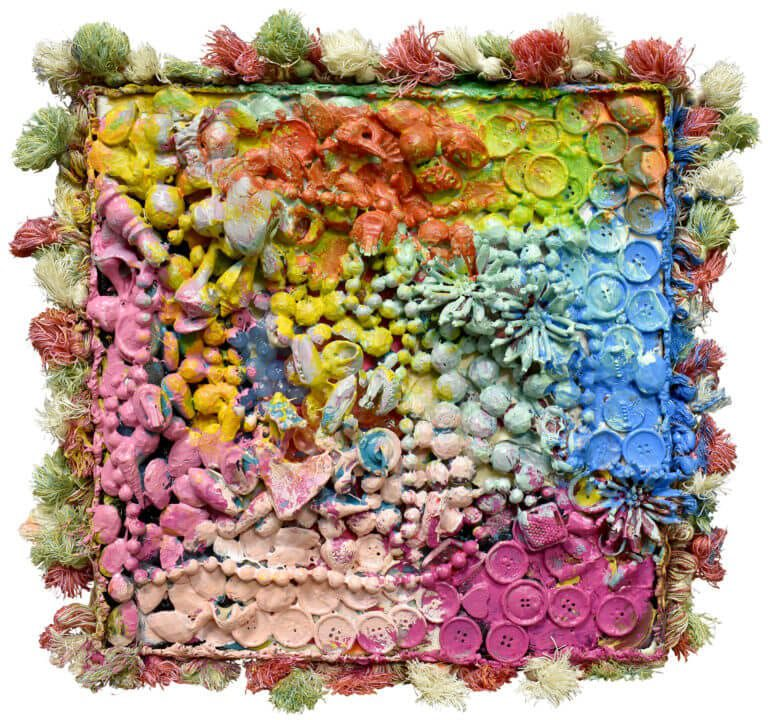 A sculpture of seashells, buttons beads, and fabric trimming on canvas