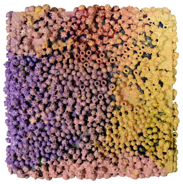 A sculpture of ceramic beads, plastic beads, paper and acrylic paint on wooden board