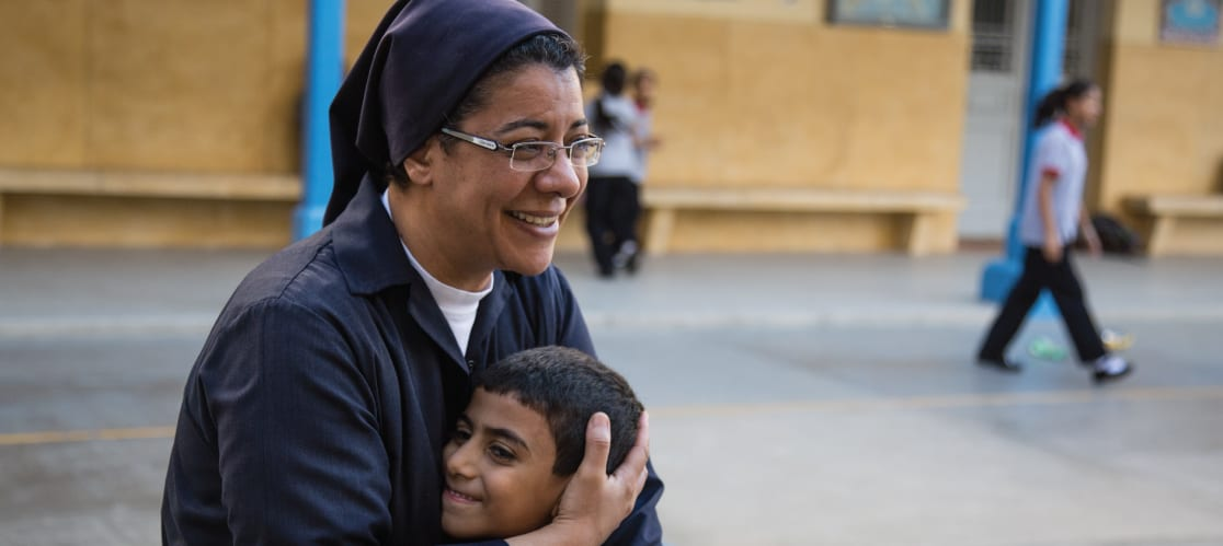 Nun hugging child in public setting, both smiling.