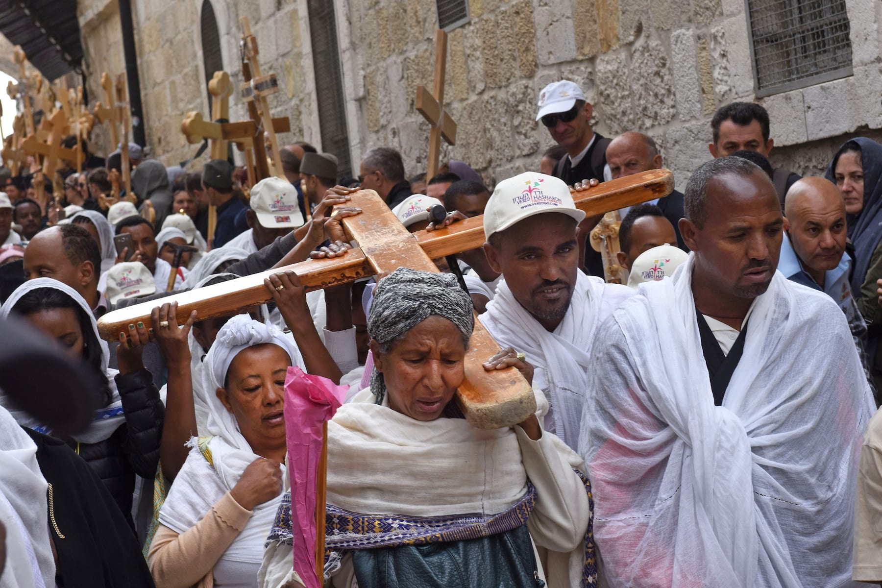 Christians from Ethiopia carry cross during procession Via Dolorosa in Jerusalem