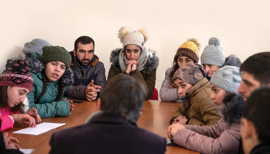 About a dozen youth gather around a table, chatting with a priest in the eastern european nation of armenia.