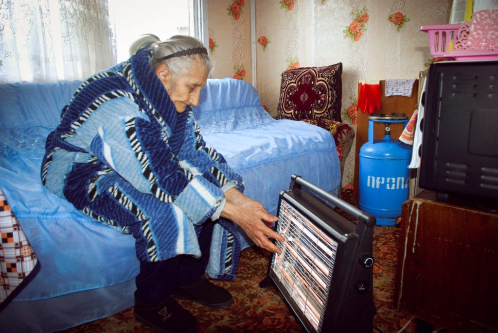elderly woman in armenia holds her hands in front of a space heater.