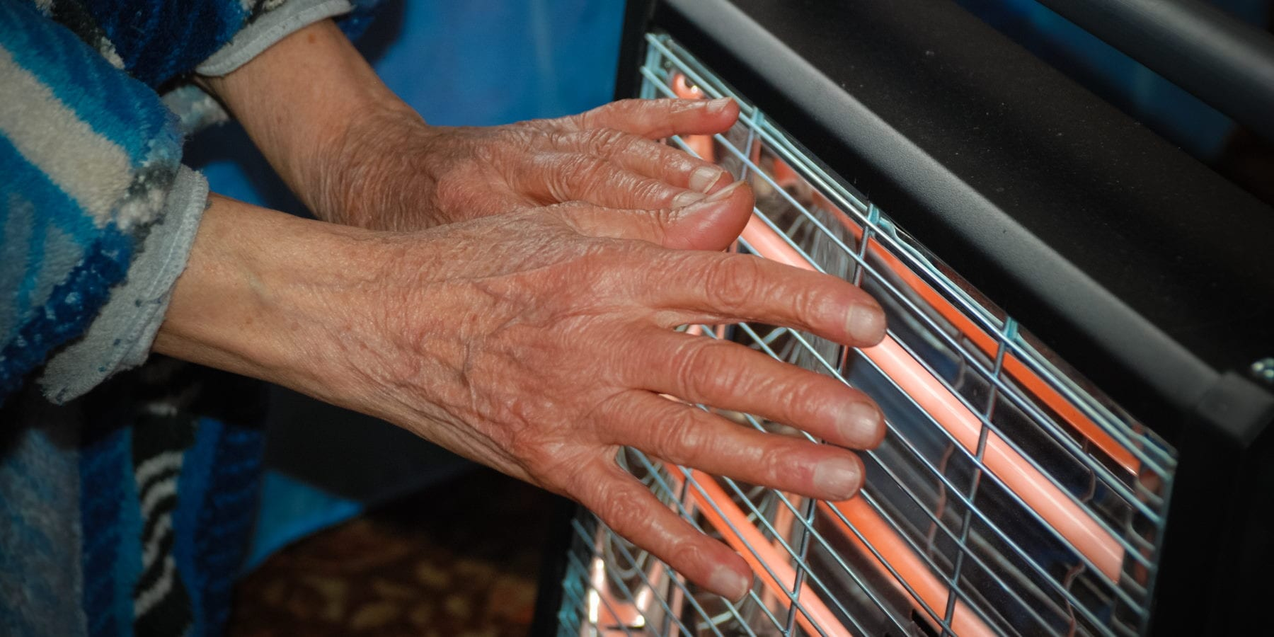 a closeup of hands warming in front of a space heater.