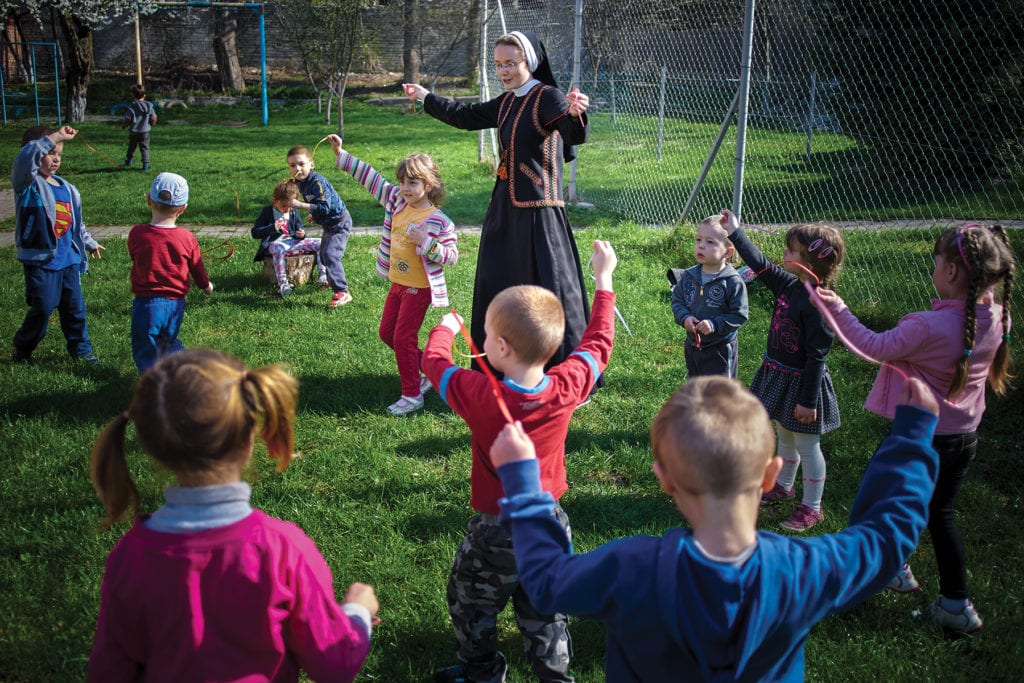 A nun plays outside with a crowd of children in the eastern european nation of ukraine.