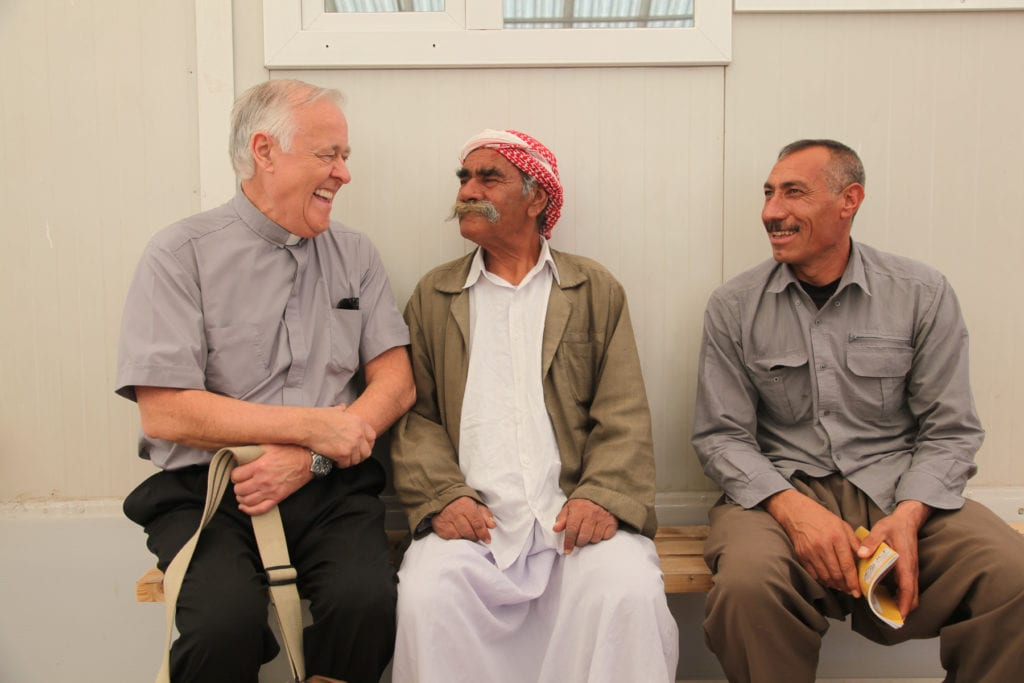 john kozar chats with two Iraqi men while seated on a bench beside them.
