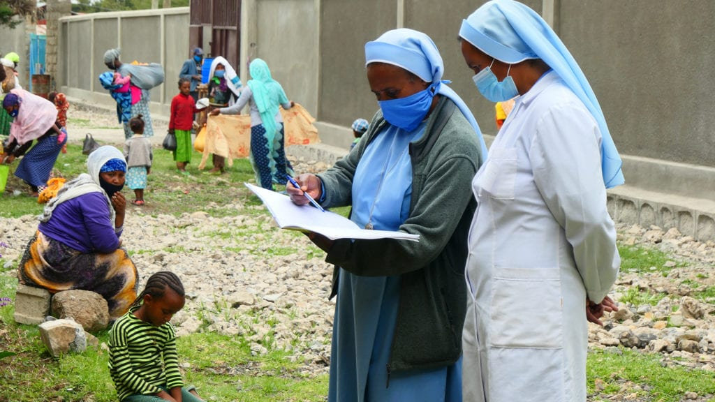 two nuns stand outside of a building, scanning an open notebook, while patients wait or walk through the area around.