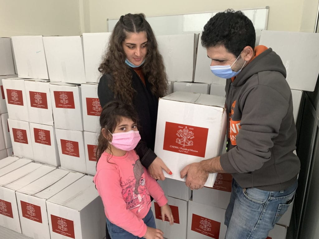 a mother, father and daughter claim a food aid box with a CNEWA label off a large stack of such boxes.