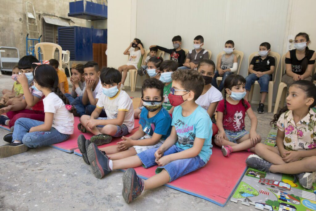 masked children sit in chairs and on the floor at a group discussion in Lebanon.