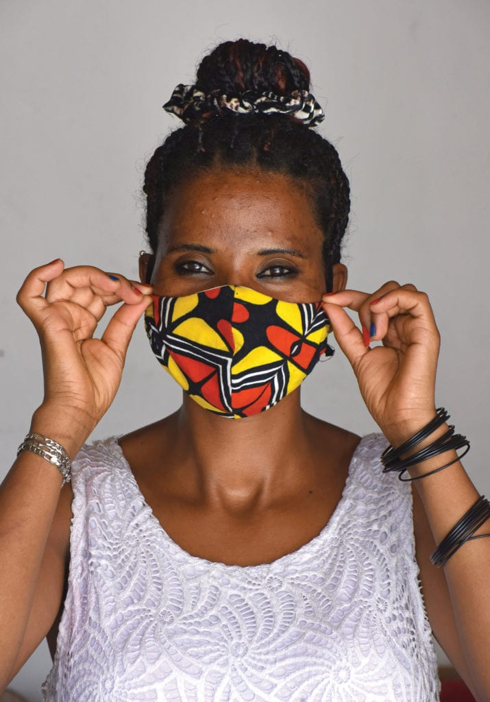 A woman models a mask she made, her smile visible in her eyes.