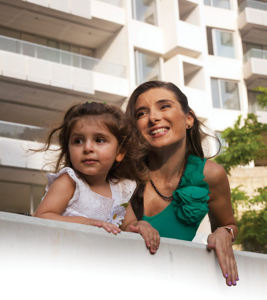 A woman and her young daughter look off at something out of frame from a small ledge or balcony.