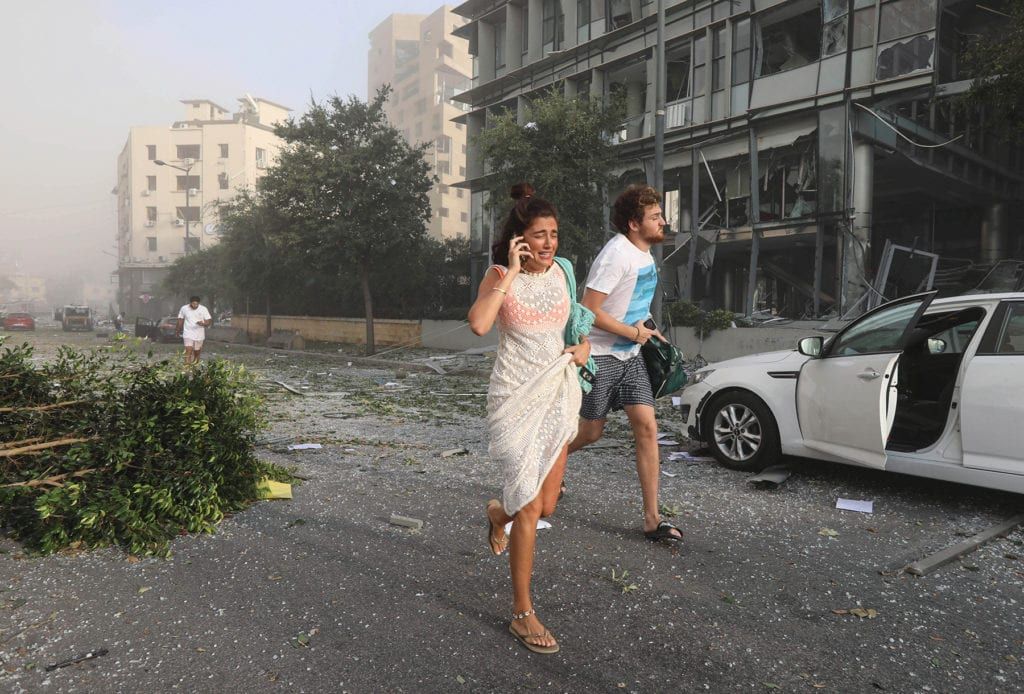 several people, including a woman speaking on her mobile phone, flee down a beirut street, smoke hanging in the air in the background.