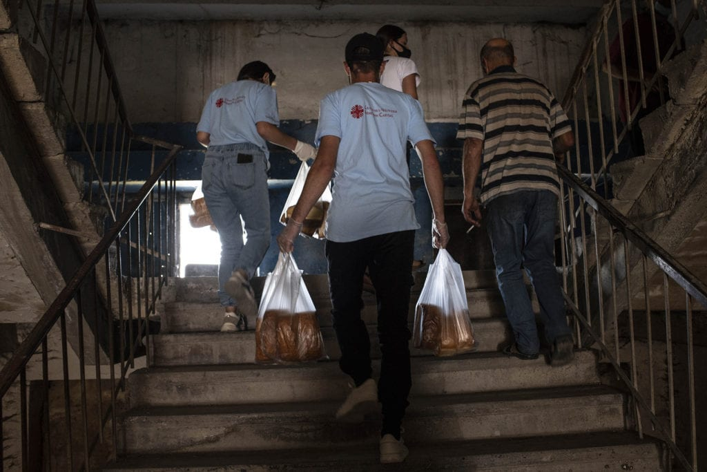 volunteers carry bags of bread up a flight of stairs.