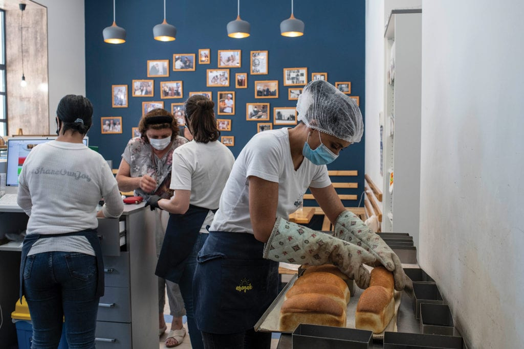a woman in a hairnet, mask and baking gloves inspects bread fresh from the oven.