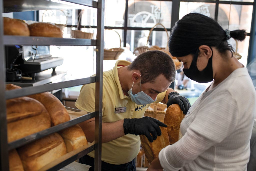 a young man in a mask and gloves takes a pair of loaves off a rack.