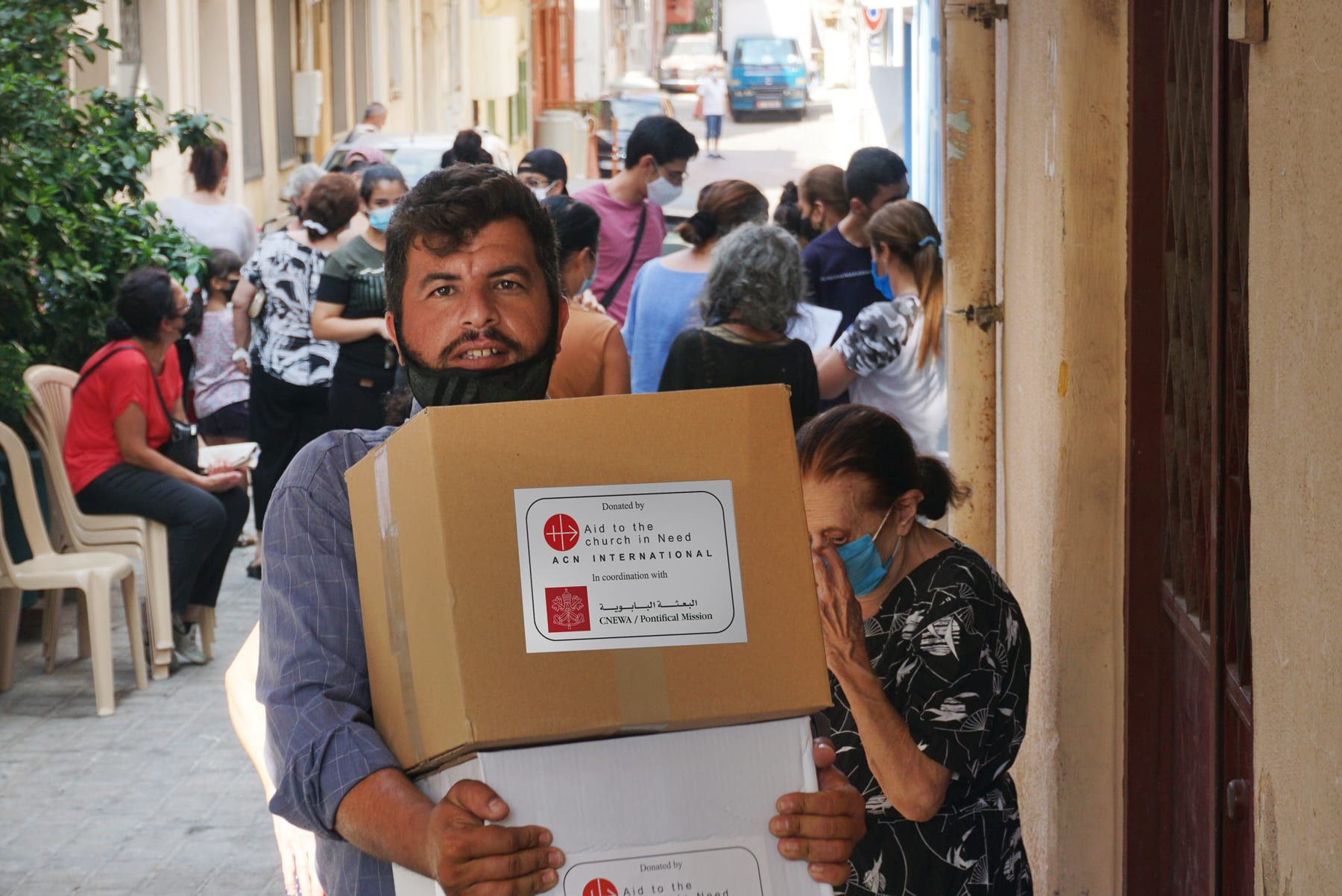 on a busy street, a lebanese man carries a box stamped with the logos of Aid to the Church in Need and CNEWA.