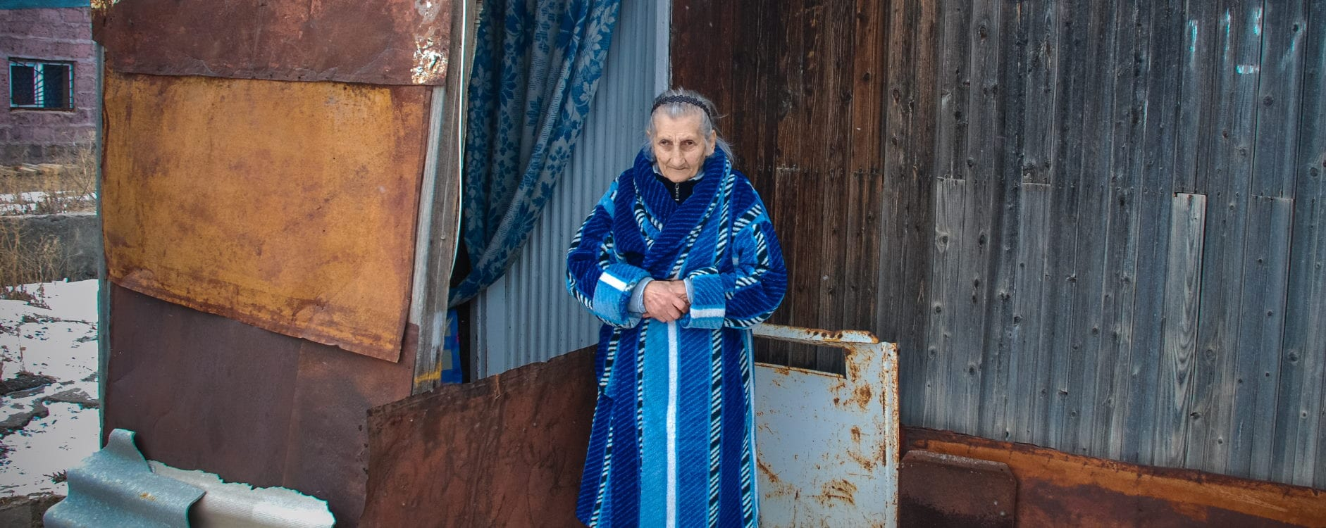 an elderly woman stands in front of a house made of rusted corrugated metal.