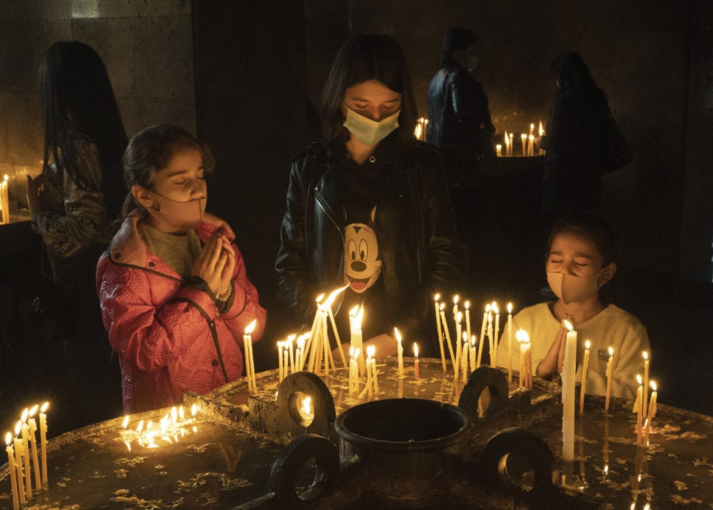 three children in masks pray before dozens of candles.