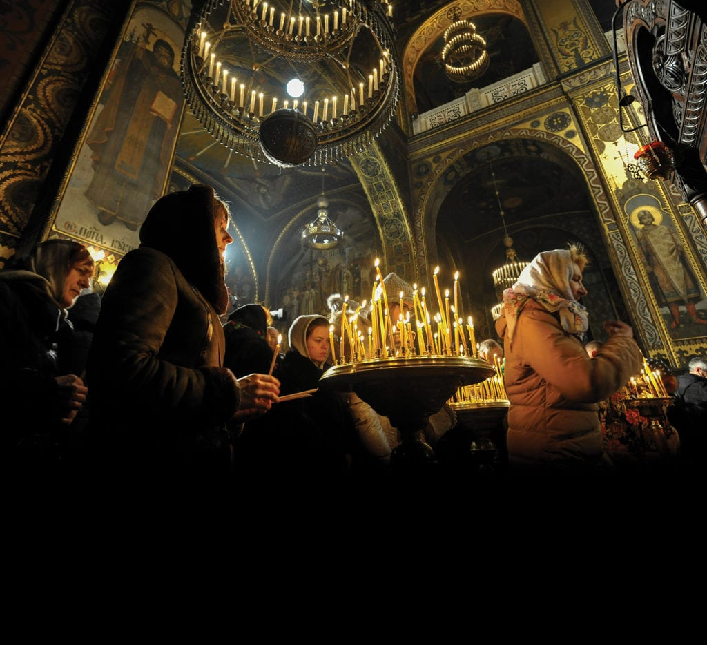 people pray in an ornate cathedral.