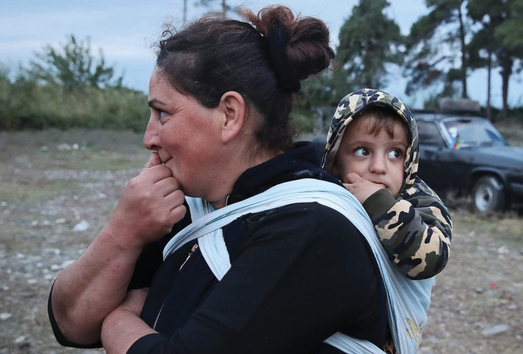 a mother stands with young child strapped to her back.