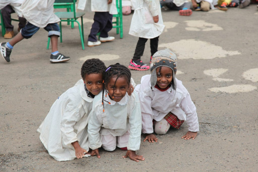 three smiling children in clean white outfits crouch outside in eritrea.