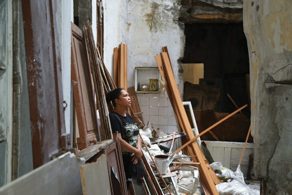 a woman stands near the rubble of her destroyed home.