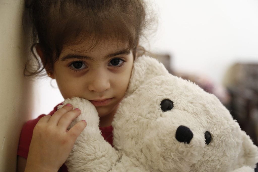 a young girl holds a teddy bear.