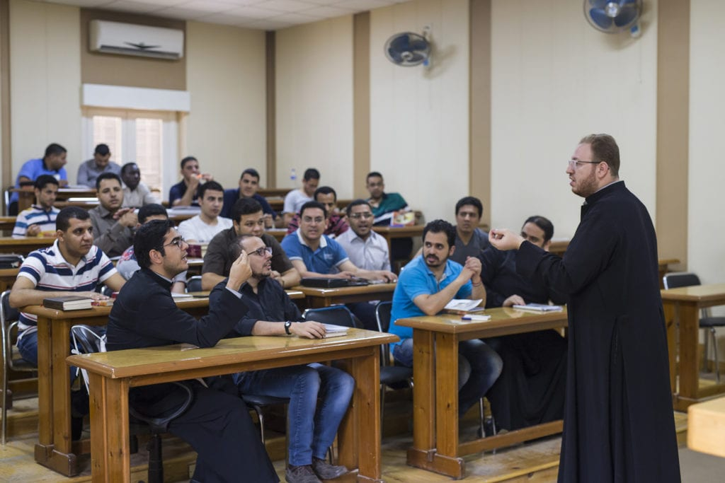 a priest lectures seminary students.