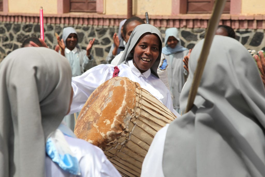 woman in veil playing a large drum outdoors.