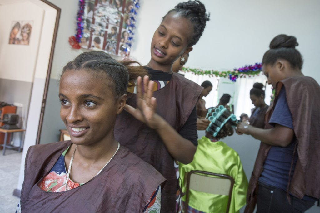 young women practice hairdressing on one another in a small salon in northeast africa.