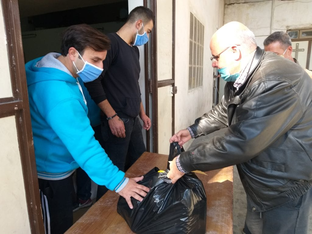Man receives food packages at the Marist Brothers' Center in Aleppo