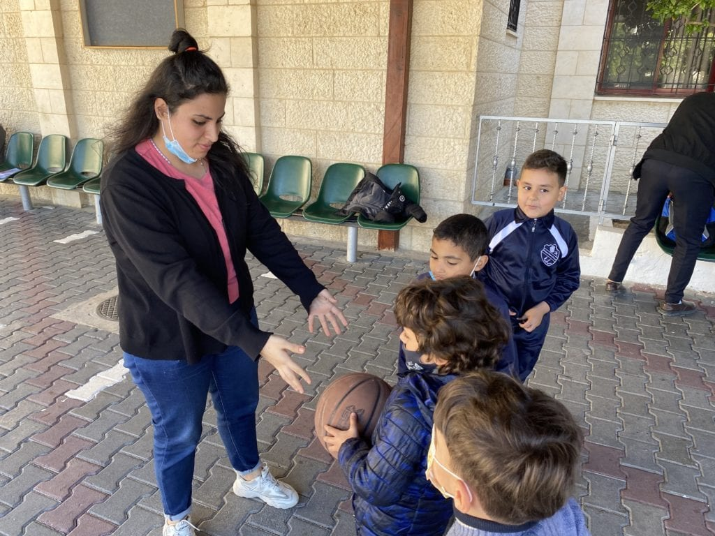A volunteer teaches students at Rosary Sisters School language skills through games
