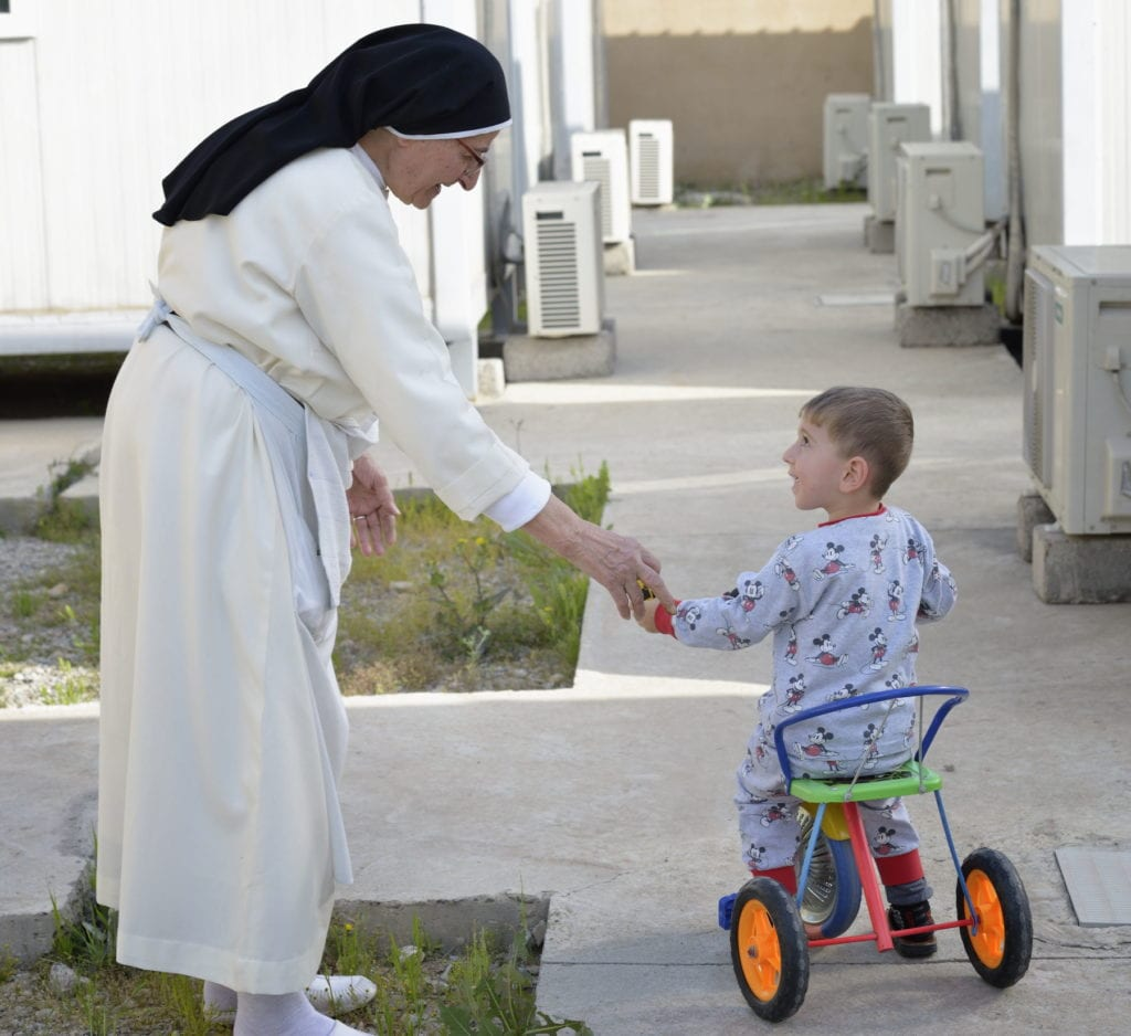 a nun greets a youngster on a tricycle in iraq.