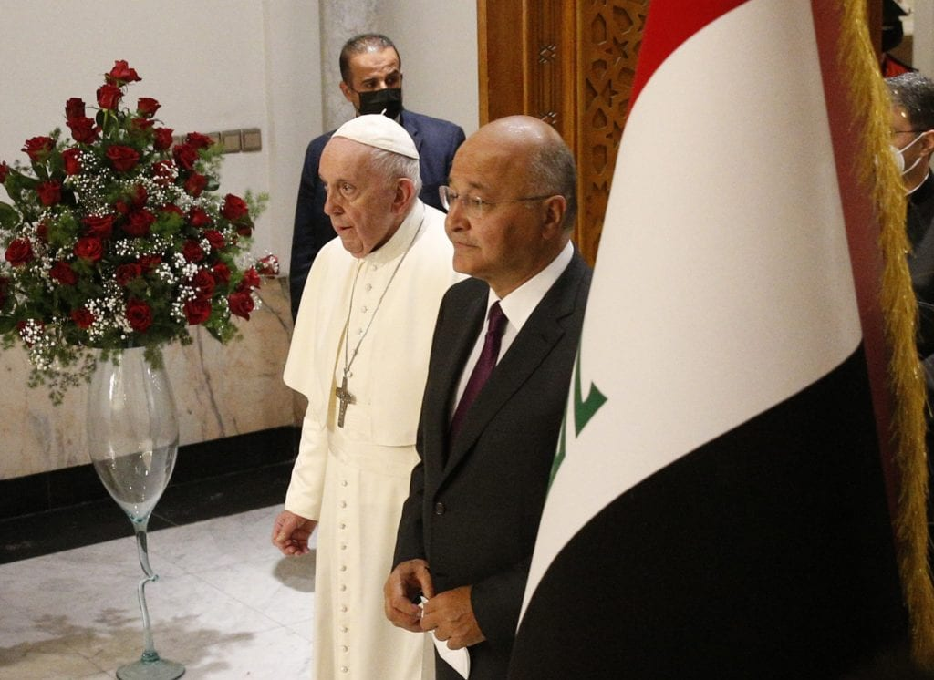Pope Francis and Iraqi President Barham Salih arrive for a meeting in the hall of the presidential palace in Baghdad