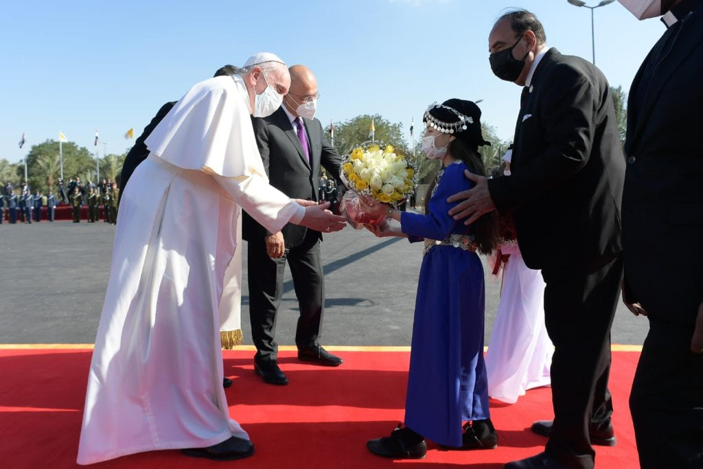 Pope Francis receives flowers from children during a welcoming ceremony with Iraqi President Barham Salih at the presidential palace in Baghdad on 5 March
