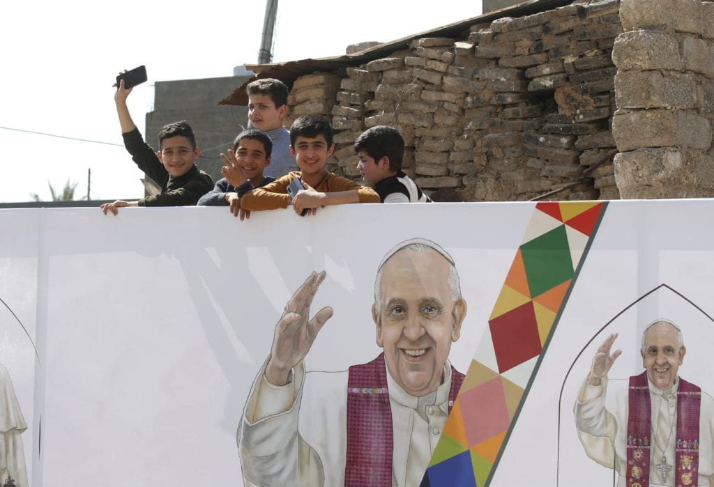 Children are seen near an image of Pope Francis during the pope's visit with the community at the Church of the Immaculate Conception in Qaraqosh, Iraq