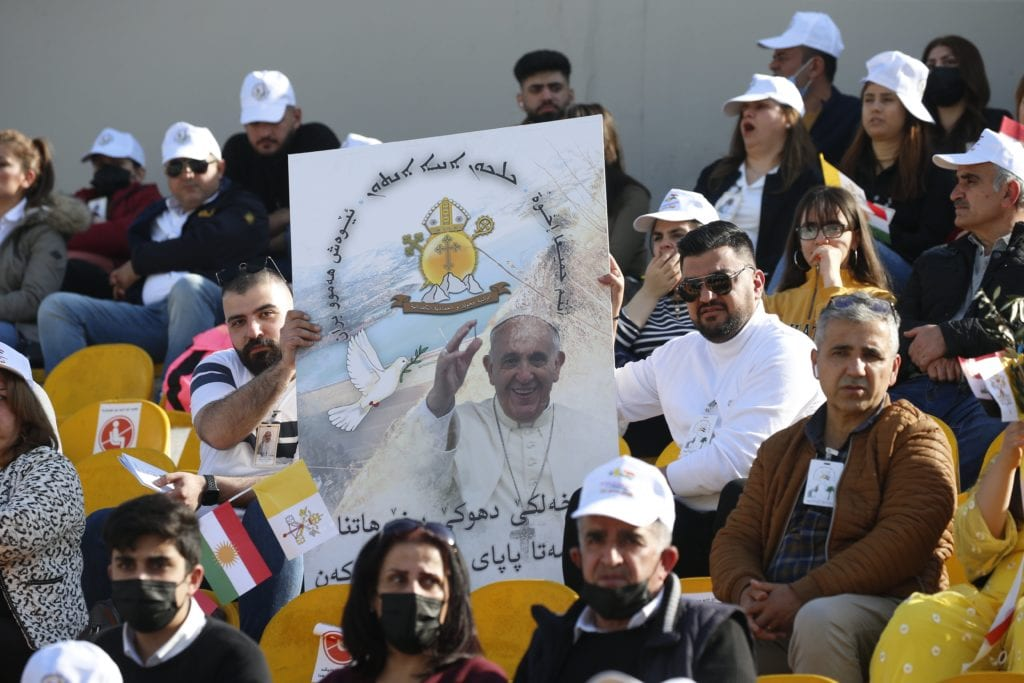 Men display a poster with an image of Pope Francis as the wait for him to celebrate Mass at Franso Hariri Stadium in Erbil, Iraq.