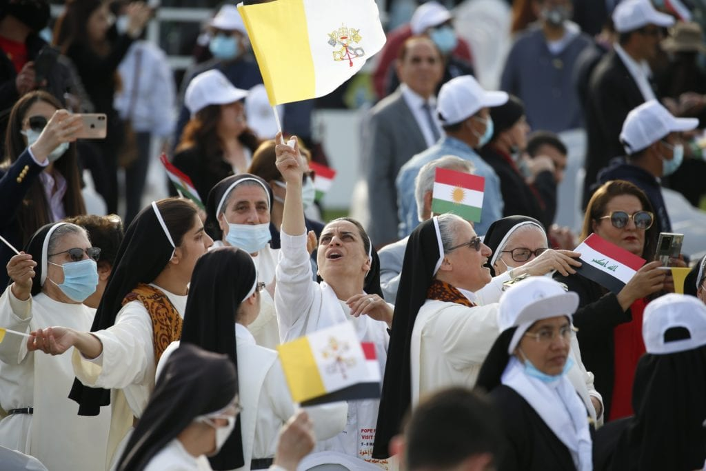 A nun waves a Vatican flag as she waits for Pope Francis to celebrate Mass at Franso Hariri Stadium in Erbil, Iraq.