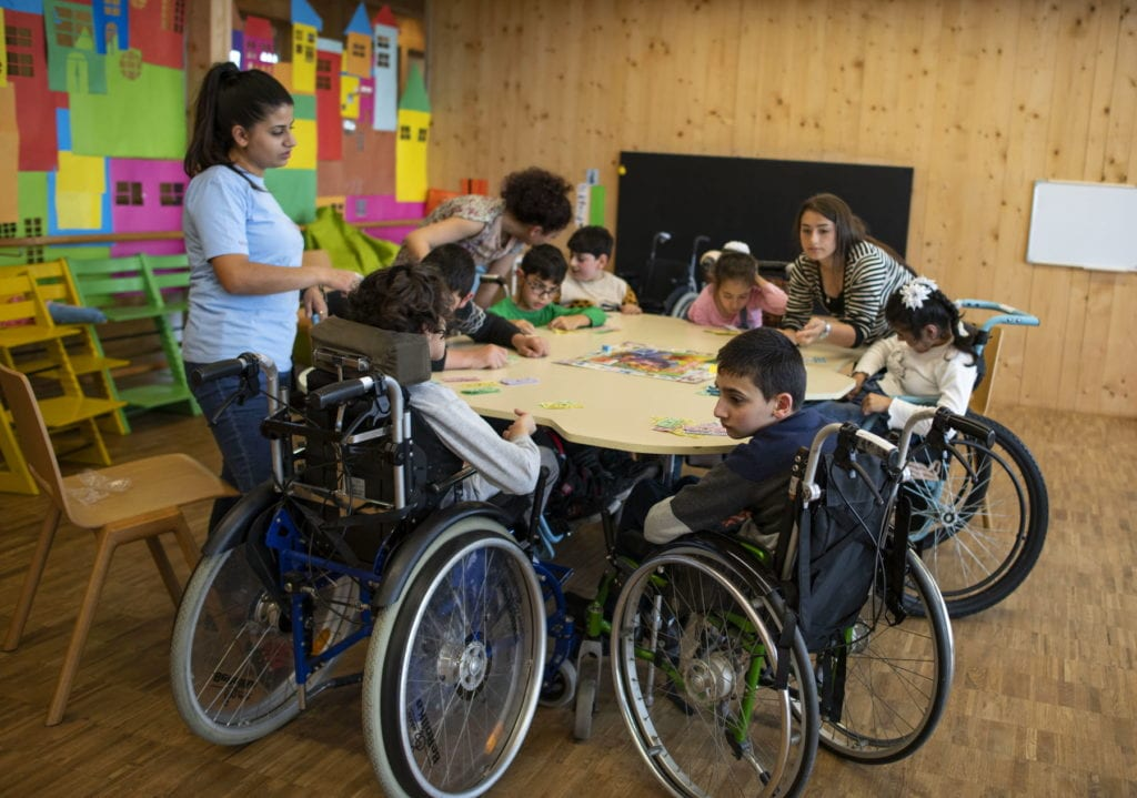 Armenian children, some in wheel chairs, sit around a large table playing a board game.