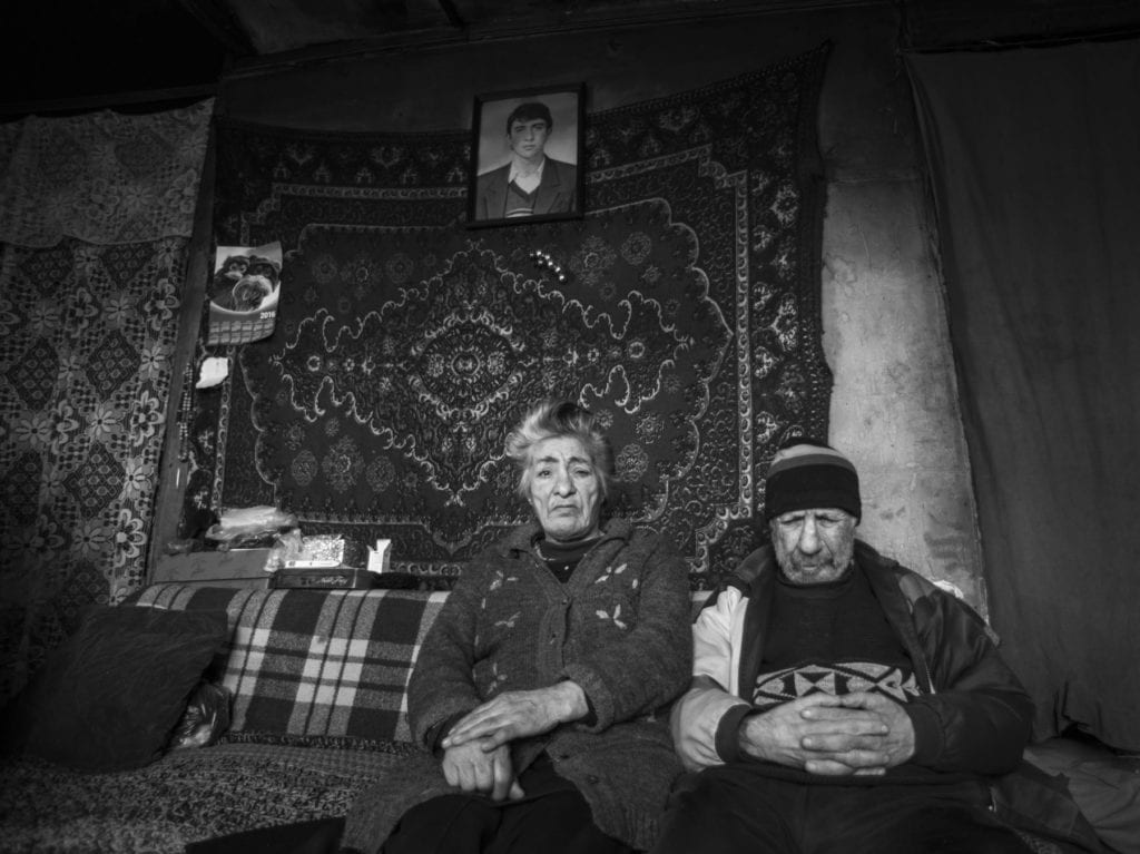 an older man and woman sit on a couch in their home in Armenia.