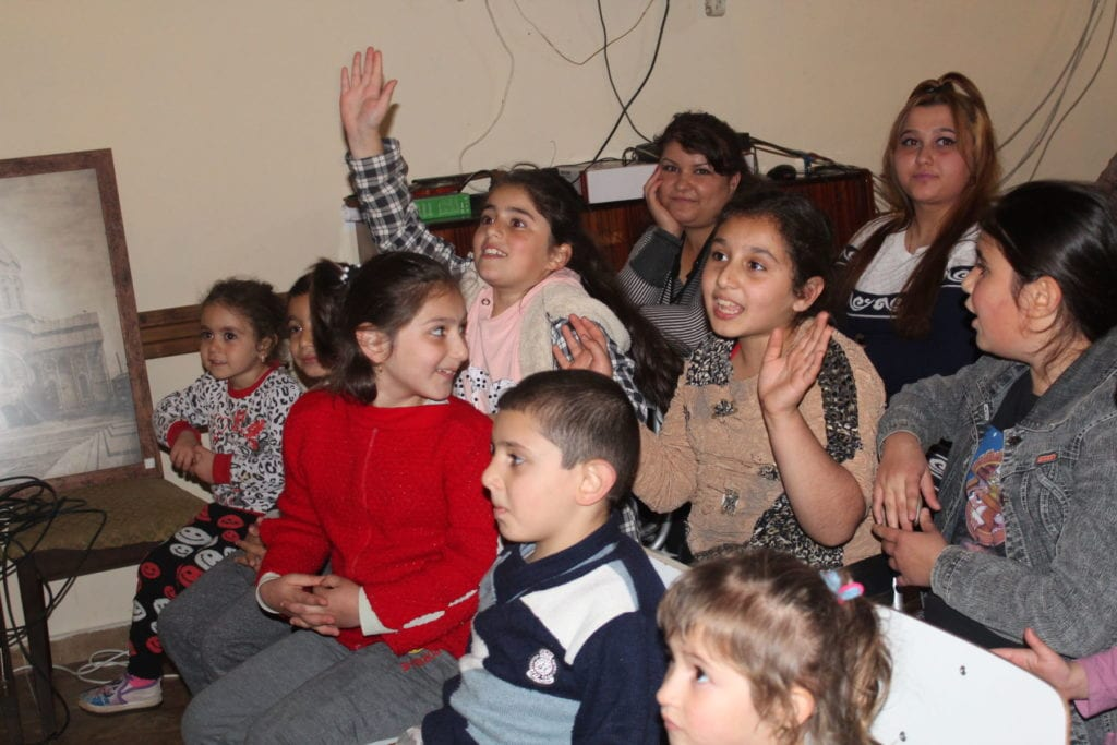 chilren raise their hands and call out during a lively exchange.