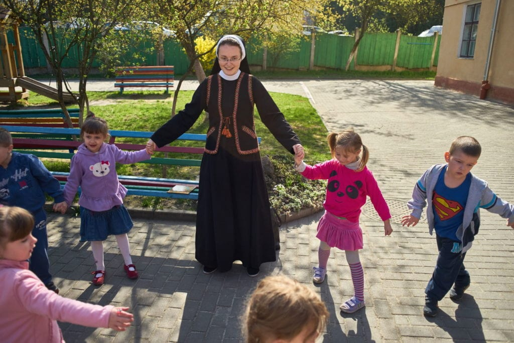 a Ukrainian nun plays with young children outdoors.
