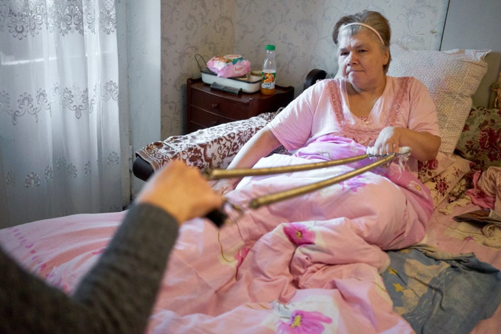 a Ukrainian woman pulls on an exercise spring held by a nurse.