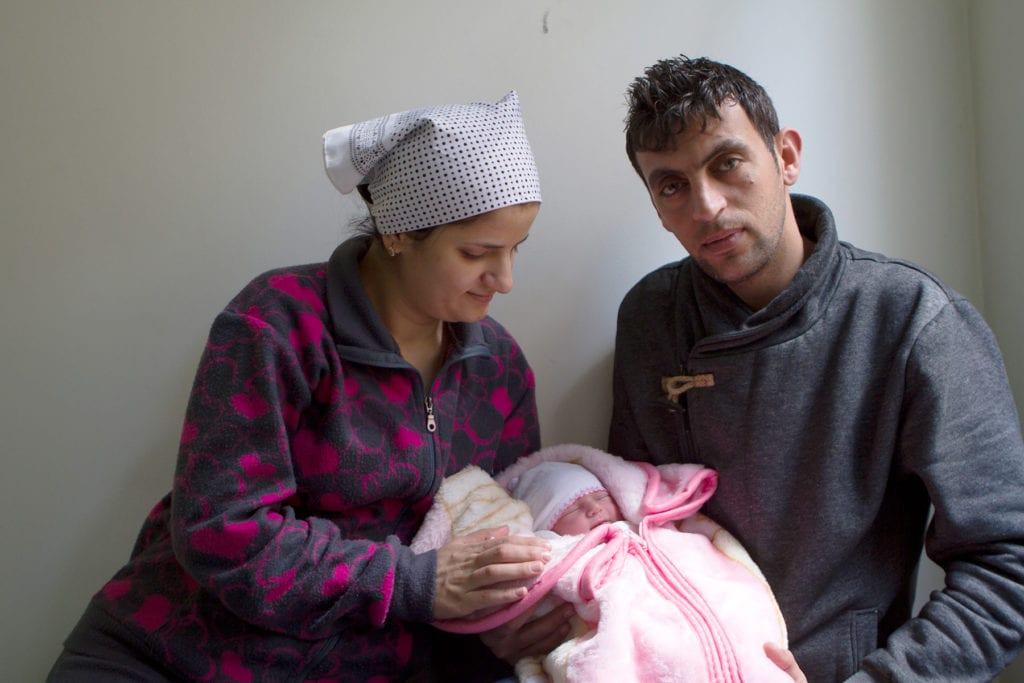 a young couple hold their swaddled newborn in Jordan.