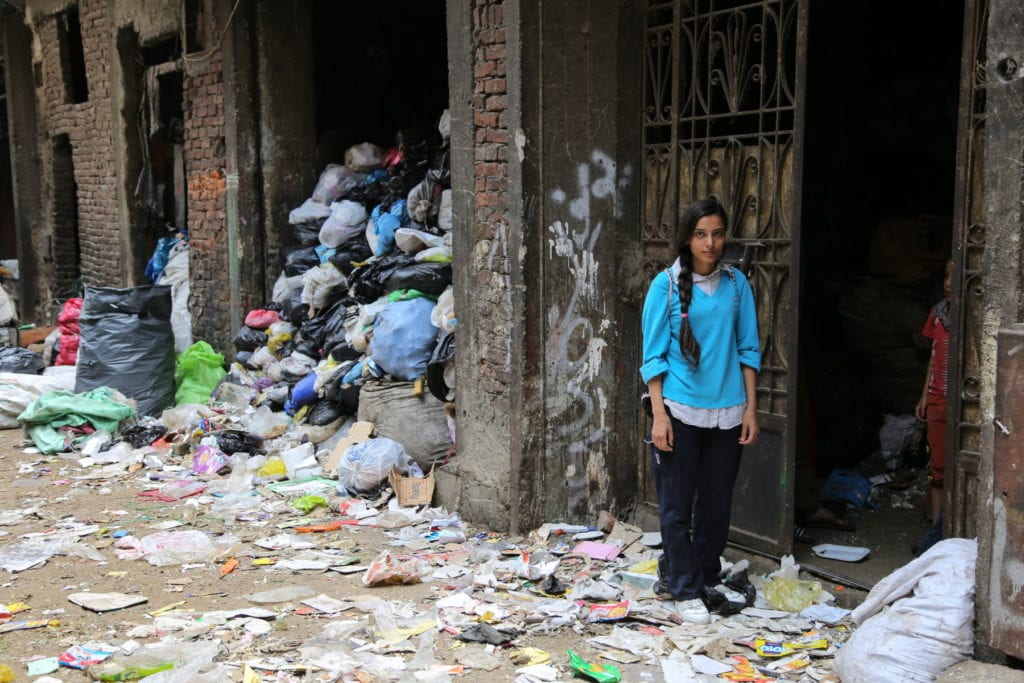 a young woman stands near a door on a street covered in trash in Cairo, Egypt.
