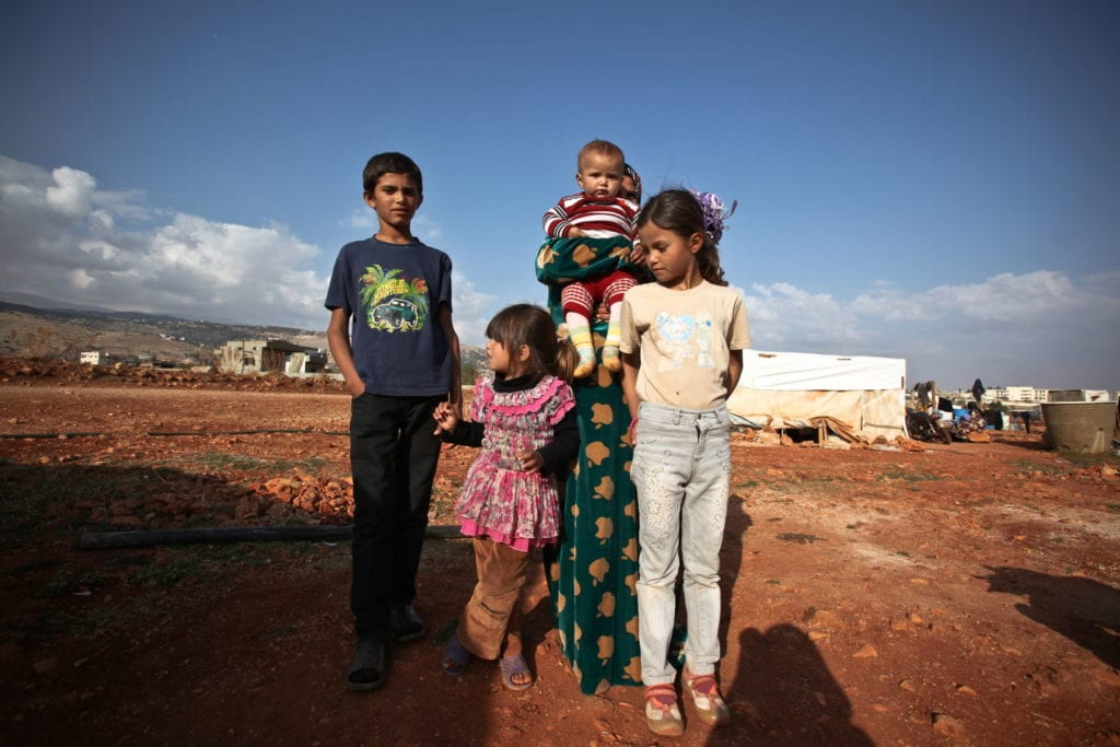 syrian refugees stand near their temporary home in Lebanon.