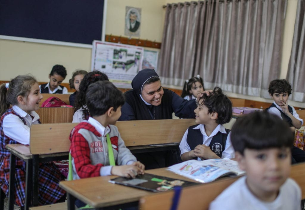 A religious sister sits in the middle of a classroom, tousles the hair of a smiling student in Palestine.