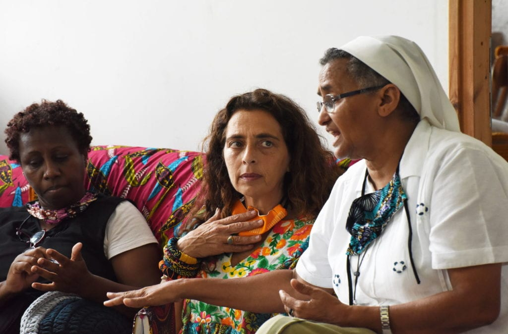 a nun sits with two migrant women in Israel.