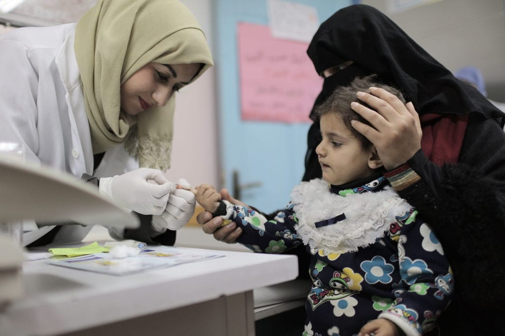 a child receives a checkup in a clinic in Palestine.