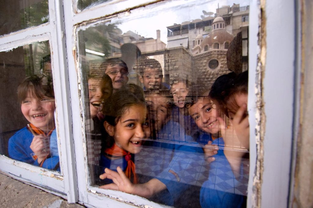 students at a Catholic school in Aleppo wave through a window.