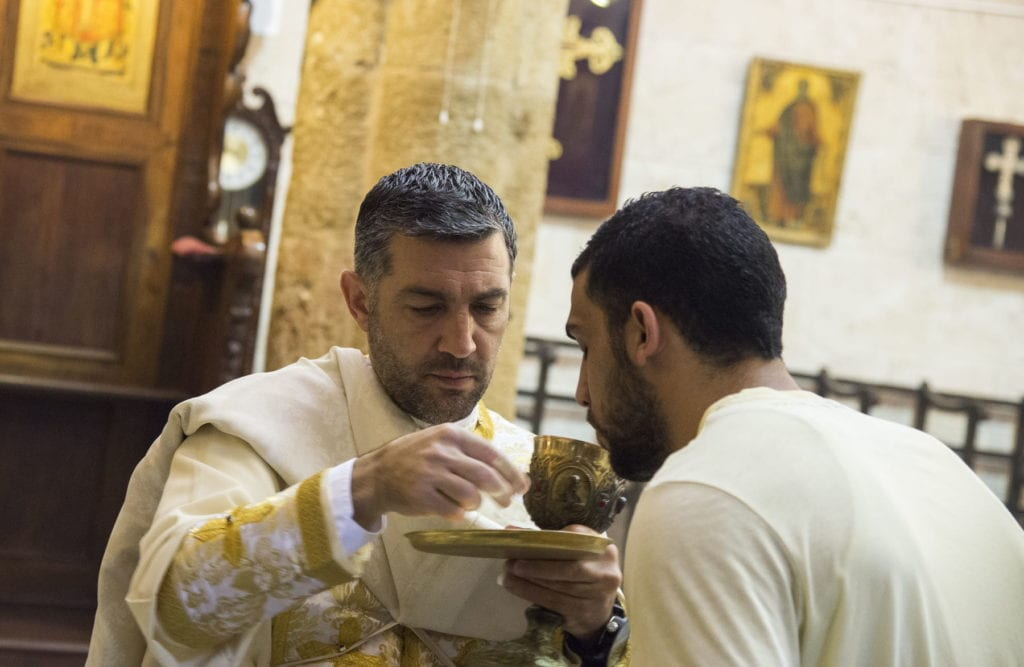 a priest gives communion in a church in Israel.